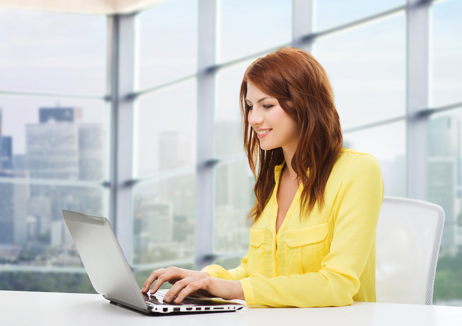 people, business and technology concept - smiling young woman with laptop computer sitting at table